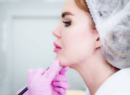 Beautician draws the contours of a white pencil on the face of the patient. Schematic marking before contouring. Close-up preparation of the face for cosmetic plastic surgery. Copy space Banco de Imagens - 142076417