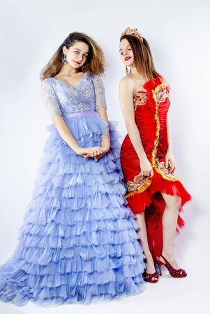 Cute young women wearing magnificent blue and red dresses. Sisters-friendly scenery. Carnival concept. Isolate