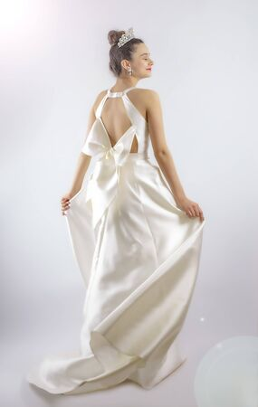Portrait of a beautiful girl in a wedding dress. Dancing Bride, gray background. Isolated