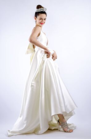 cheerful young bride holding the hem of her dress and funny grimacing on gray background. Tricks and insidiousness concept. Isolated Archivio Fotografico