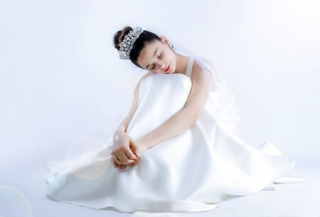 A bride sitting on the floor with her eyes closed. Happiness and fulfillment of dreams concept. Copy space