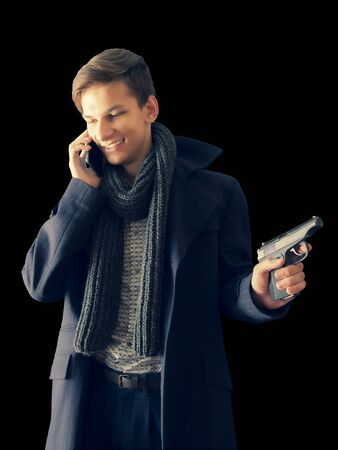 Mysterious undercover young man-gangster holding a gun and wearing a dark coat has a nasty phone conversation isolated on black background