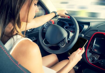 Young woman holding blank screen cell phone while driving car. Female driver hand on steering wheel, checking out her smartphone in moving vehicle. Dont text and drive concept. Close up, background.