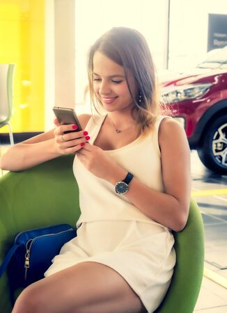 Young woman getting happy news in her phone in the car dealership. Happy face of a girl sitting on a visitor chair with her phone in hands.