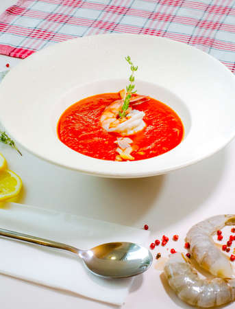 Delicious cold tomato soup or gazpacho with shrimps in a white plate on a white table. Decor. Top view. Selective focus. Super short focus