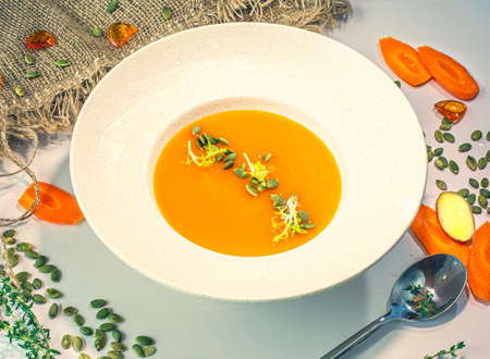Pumpkin and carrot soup with cream in a white ceramic plate. Top view.Decor. Selective focus. Super short focus 免版税图像