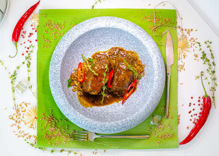 Stewed beef cheeks with spelled in a marble gray plate on a green tablecloth. Decor. Selective focus. Super short focus Reklamní fotografie