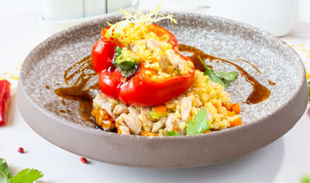 Chicken breast with bulgur baked in pepper in a gray ceramic plate in a restaurant. Selective focus. Super short focus