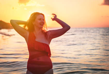 carefree woman in red swimsuit dancing at sunset on the beach. mature woman relaxation vitality healthy lifestyle. Copy space