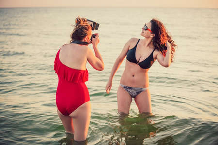 Middle aged mother and daughter teenager in beachwear on the seashore with photocamera taking photo. Professional photographer photographs dark-haired model at the seaside