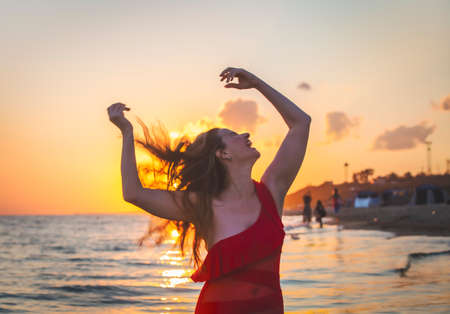 carefree woman in red swimsuit dancing at sunset on the beach. mature woman relaxation vitality healthy lifestyle