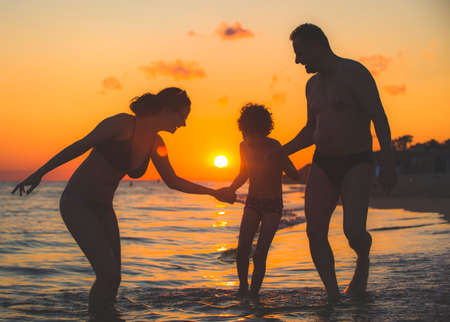 Dark silhouette of a happy family on a sunset.Father, mother, baby son walking along the sandy beach.Family having fun on the beach.Travel lifestyle, parents, dad with children on summer vacation.