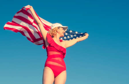 Beautiful cheerful blonde woman holding an American flag on the beach. A middle-aged woman in a red bikini is patriotically enthusiastic. Travel. USA flag. Copy space Reklamní fotografie
