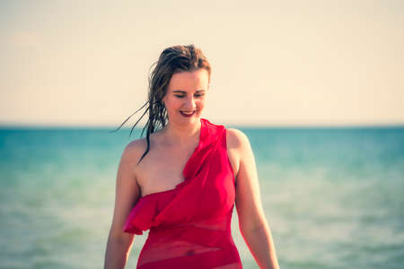 A young slender, beautiful European middle-aged woman Young beautiful woman in red swimsuit with wet brown hair coming out of the sea
