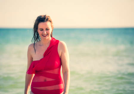 A young slender, beautiful European middle-aged woman laughs, mature brunette in red swimsuit enjoying summer vacation. Freedom and cheerfulness concept. Copy space