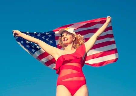 Beautiful cheerful blonde woman holding an American flag on the beach. A middle-aged woman in a red bikini is patriotically enthusiastic. Travel. USA flag