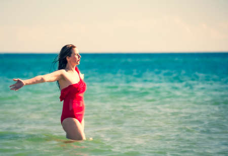 A young slender, beautiful European middle-aged woman is swimming in the sea, a mature brunette in a red bathing suit is enjoying her summer vacation. Freedom and cheerfulness concept. Copy space