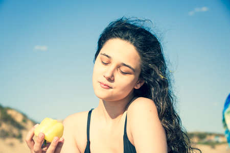 Brunette teen girl in a black swimsuit sitting by the sea, eating yellow pepper, healthy snack and vitamin food. Hot summer and sand.Wet dark wavy hairs. Anapa