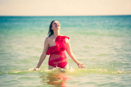 A young slender, beautiful European middle-aged woman is swimming in the sea, a mature brunette in a red bathing suit is enjoying her summer vacation. Freedom and cheerfulness concept
