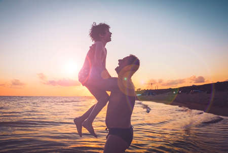 Black silhouettes of father and son against the sunset sky. Mature father and son playing on beach. Dad raised his son in his arms. They are laughing