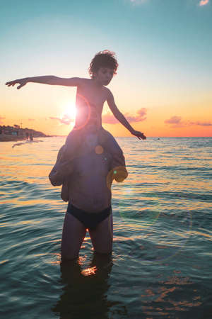 Black silhouettes of father and sana against the sunset sky. Mature father and son playing on beach. Curly Boy rising up hands imitating a flight at bright sunset through the shining sun.