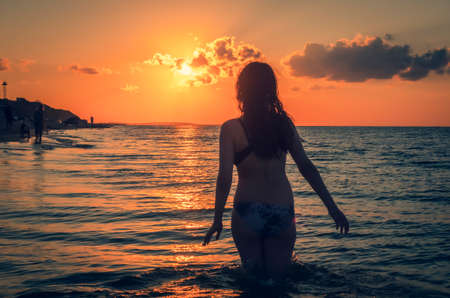 European beauty woman silhouette at sunset with long healthy wet hair enjoying nature and walking in the water. Model from behind relaxing at landscape with a tent city on a sandy beach. Reklamní fotografie