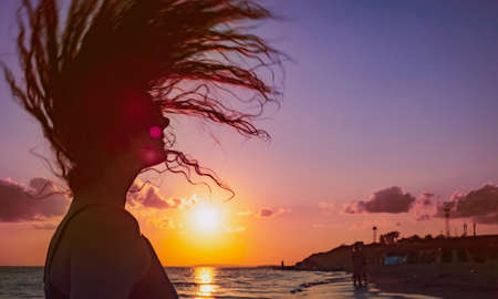 the beautiful girl with long hair costs in the sea against the sunset sun. Copy space Reklamní fotografie