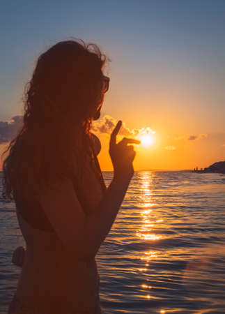 View of a beautiful sunset over the sea. Beautiful young female teenager relaxing and enjoying sun at foreground sunset. Pretty happy lady enjoying summer outdoors. Focus on the sun Reklamní fotografie