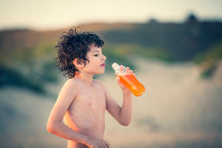 Close up side view of Cute kid drinking cold drink on the beach, Little boy drinking sweet carbonated water from the neck of a plastic bottle. Child drinking. Reklamní fotografie