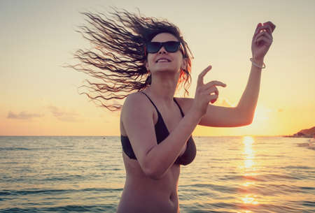 the beautiful girl with long hair costs in the sea against the sunset sun