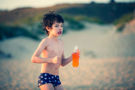 A little boy in a swimming trunks and a bottle of juice in his hand is shaking from the cold. The child is cold from the cold drink.