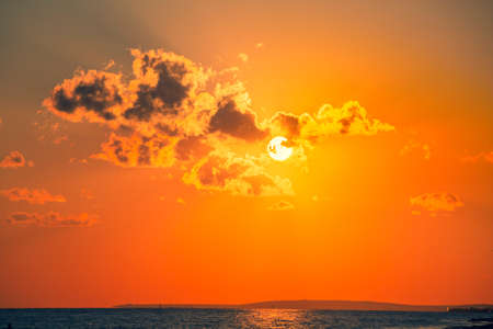The sun with dark clouds in the orange red sky, the power of nature. Setting sun aa cloudy sky. Reklamní fotografie