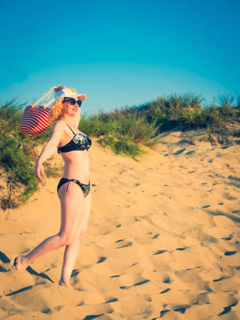 Pretty middle aged woman in black shiny swimsuit enjoying sand tropical beach. Travel and beach vacation concept. Copy space