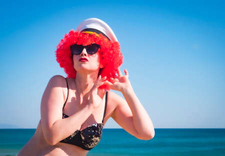 Close up portrait of a crazy middle aged lady in red wig, black shiny swimsuit eavesdrops against the sky. Middle aged woman in a navy cap on a tropical resort