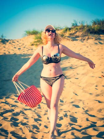Pretty middle aged woman in black shiny swimsuit enjoying sand tropical beach. Travel and beach vacation concept