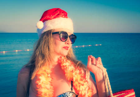 Beautiful young woman in Santa Hut, Hawaii accessory and bikini on beach. Christmas vacationPretty middle aged woman in black shiny swimsuit enjoying sand tropical beach