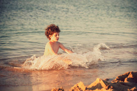 Cute curly male kid playing game at the beach. Little boy makes splashes in sea water. Funny games during summer vacation. Child having fun with sand at coast. Leisure, games and vacation Standard-Bild