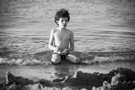 Cute curly male kid playing game at the beach.Little boy play with sand on summer beach.Funny games during summer vacation. Child having fun at coast. Leisure, games and vacation.Black and white photo Standard-Bild