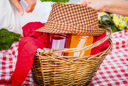 Lunch in the park on the green grass. Summer sunny day and picnic basket. With juice in plastic bottles. Healthy sober lifestyle concept concept