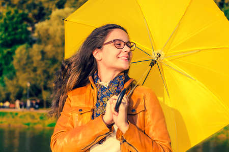 A smiling girl with a yellow umbrella is hiding from the rain.Beautiful brunette woman with glasses with umbrella on a rainy day.Attractive young woman carrying umbrella while standing in the park