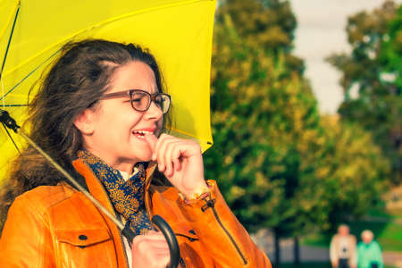 Shocked stylish young girl in leather jacket and with a yellow umbrella looking into the distance in the autumn Park. Autumn time. Copy space Standard-Bild