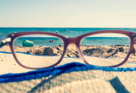 Close-up Of Beach And Sea Seen Through Glasses On Sunny Day