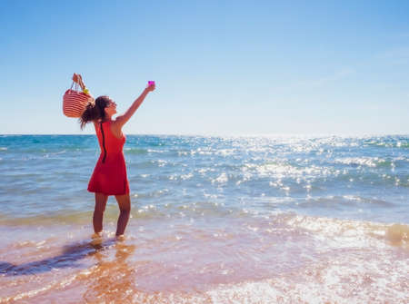 a woman brunette in a hat standing in the water on a sandy beach with a plastic glass in her hand on a clear summer day. vacation on sunny day. Copy space