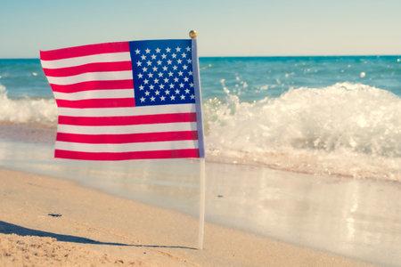 USA patriotic background with American flag on a sandy beach. Reklamní fotografie
