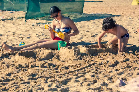 Bored kids on the sandy beach. Boredom and satiety concept