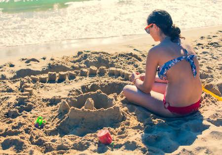 Happy teenage kids playing with sand on the seaside Standard-Bild