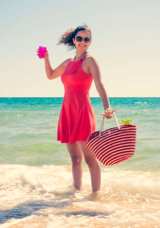 a woman brunette in a hat standing in the water on a sandy beach with a plastic glass in her hand on a clear summer day. vacation on sunny day