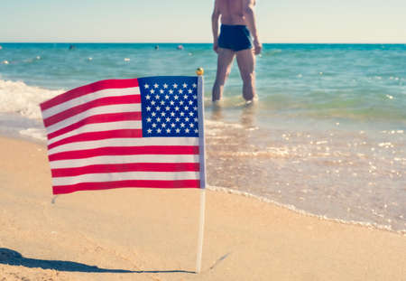 USA patriotic background with American flag on a sandy beach. Male torso in the background