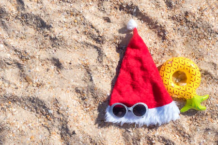 Santa Claus hat with masquerade goggles on sea coast. Christmas vacation On Sunny Day Standard-Bild