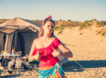 Beautiful caucasian woman with african braids enjoying the freedom in free camping at the beach and tent alternative people travel concept. Ok gesture